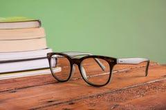 Livres et verres sur une table en bois Photos stock