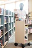 Livres heureux de With Trolley Of de bibliothécaire dans la bibliothèque Photos stock