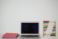 Livres, ordinateur portable et abbacus Photo stock