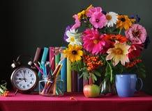Livres, réveil et un bouquet sur la table Le jour du ` s de professeur Image libre de droits
