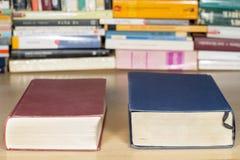 Livres rouges et bleus sur un bureau en bois clair Image stock