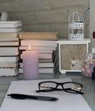 Livres sur la table, une bougie brûlante lilas, verres, papier, stylo, boîte photographie stock