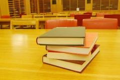 Livres sur le bureau dans la bibliothèque Photo stock