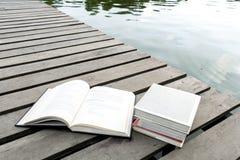 Livres sur le plancher en bois le pont du secteur de bord de l'eau touchant l images stock