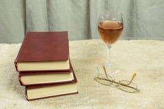 Livres, un verre de vin et verres Photos libres de droits