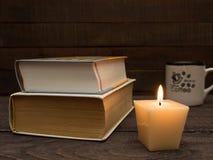 Livres, une tasse de café fort et une bougie sur une table en bois Photos libres de droits