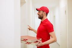 Livreur avec des boîtes à pizza sonnant la sonnette Images libres de droits