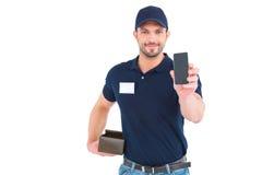Livreur beau montrant le téléphone portable image stock