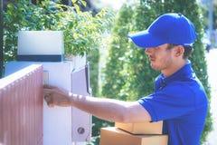 Livreur dans le bleu remettant des paquets à la maison images stock