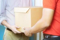 livreur de colis d'un paquet par un service et ?troitement client de main acceptant une livraison images libres de droits