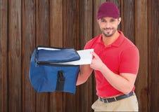 Livreur de pizza avec les boîtes de sac et de pizza de la livraison Fond en bois Images stock