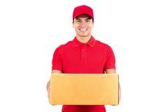 Livreur de sourire portant une boîte de colis images libres de droits