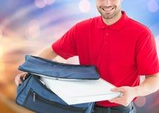 Livreur heureux avec les boîtes de sac et de pizza de la livraison Allume le fond Photographie stock
