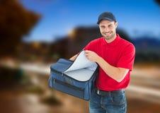 Livreur heureux de pizza avec le sac de la livraison dans la ville à la soirée Image stock