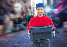 Livreur heureux de pizza avec le sac de la livraison dans la ville avec des lumières Photographie stock libre de droits