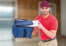 Livreur heureux de pizza avec le sac de la livraison et boîtes devant l'ascenseur Image stock
