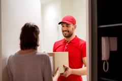 Livreur heureux donnant la boîte de colis au client image stock