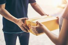 Livreur livrant tenant la boîte de colis image stock