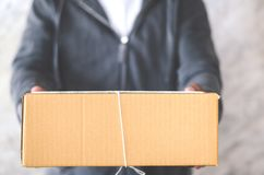 Livreur portant une boîte de colis photographie stock libre de droits