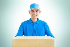 Livreur portant une boîte de colis de carton photographie stock libre de droits