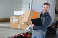 Livreur tenant la boîte dans le camion avant images stock