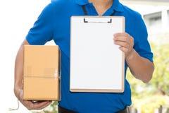 Livreur tenant une boîte de colis et un livre blanc sur le presse-papiers Images libres de droits