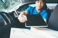 Livrez l'homme tenant le comprimé avec des colis sur le siège dans la voiture photographie stock