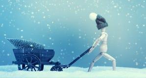 Livrez un arbre de Noël, marionnette avec le chariot image stock