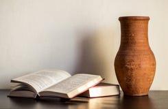 Livro aberto com vasilha de barro em uma tabela de madeira Fotos de Stock Royalty Free
