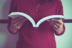 Livro aberto da mão da mulher para a leitura em casa, perto acima e a sela do foco seletivo fotografia de stock royalty free