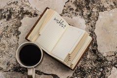 livro aberto do caderno da lista de objetivos pretendidos e uma xícara de café em um outd de pedra imagem de stock royalty free