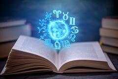 Livro aberto na astrologia em um fundo escuro O globo mágico de incandescência com sinais do zodíaco na luz azul imagens de stock