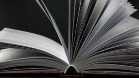 Livro aberto no fundo preto As páginas que balançam levemente video estoque