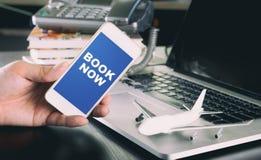Livro agora na tela do smartphone para a agência de viagens imagem de stock