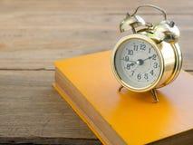 Livro amarelo com o despertador do vintage na tabela de madeira Fotografia de Stock Royalty Free