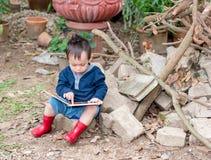 Livro asiático do conto da leitura do bebê, o sittin vermelho da bota do desgaste do menino Imagens de Stock Royalty Free