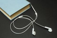 Livro azul com fones de ouvido em um fundo preto imagem de stock