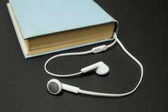Livro azul velho, e fones de ouvido brancos em um fundo preto foto de stock