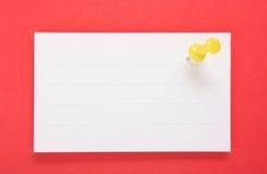 Livro Branco e Pin amarelo do impulso no fundo vermelho (com grampeamento Fotos de Stock