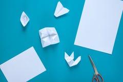 Livro Branco limpo, tesouras, papel do orig?mi: avi?o, barco e raposa em um fundo azul imagens de stock