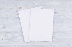 Livro Branco vazio A4, envelope na luz suave - placa de madeira azul Imagem de Stock
