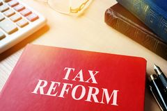 Livro com reforma fiscal do título em uma tabela imagens de stock