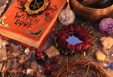 Livro da bruxa com o espelho cor-de-rosa da mágica, o pentagram e objetos místicos em pranchas fotos de stock