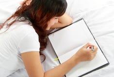 Livro da escrita da menina na cama Fotos de Stock Royalty Free