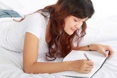 Livro da escrita da menina na cama Imagem de Stock Royalty Free