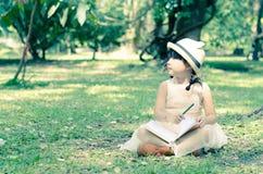 Livro da escrita da menina no parque Fotografia de Stock Royalty Free