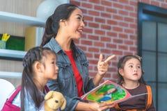 Livro da história da leitura do professor a apontar dos estudantes do jardim de infância imagens de stock
