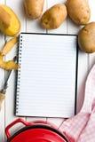 Livro da receita com batatas Foto de Stock Royalty Free