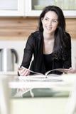 Livro da receita da leitura da mulher Fotos de Stock