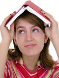 Livro da terra arrendada da menina na cabeça imagens de stock